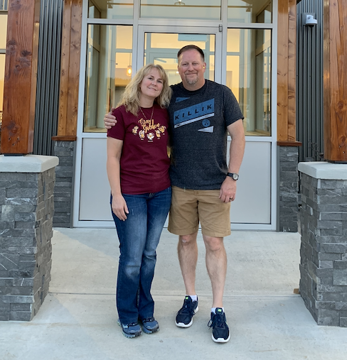 Jim and Debbie Delker smile for the camera under the entryway to their new clinic, which is made of grey brick and wooden pillars. Jim has his left arm around Debbie.