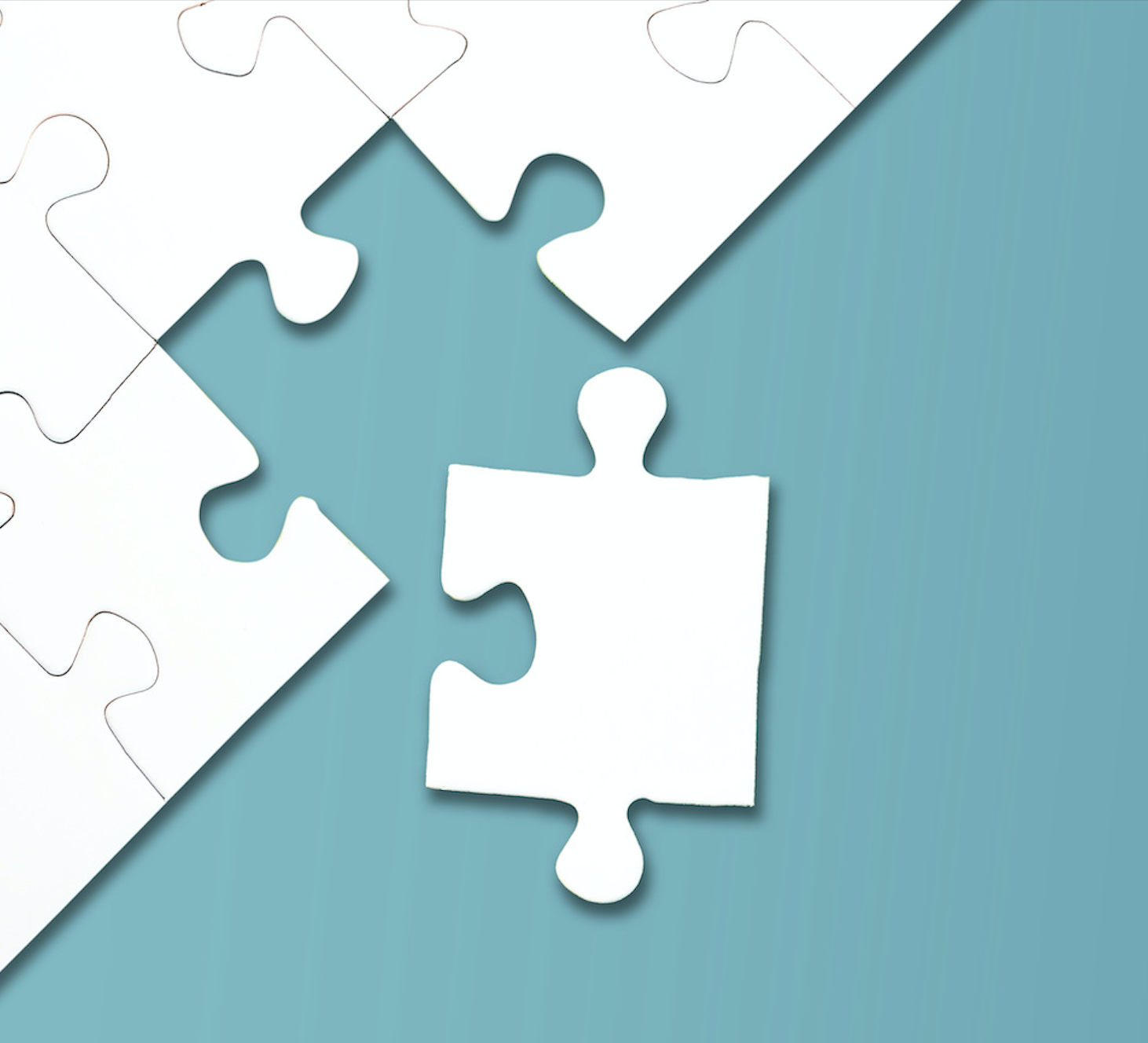 A white jigsaw puzzle against a blue background with one piece missing, but nearby
